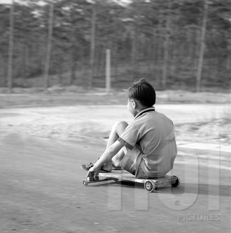 A Kid is riding down the hill on a ball bearing wooden roller board, Da Lat, Vietnam.2005