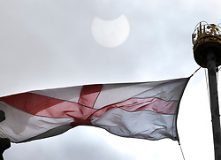 © Licensed to London News Pictures. 10/06/2021. London, UK. The moon passes in front of the sun during a partial eclipse viewed next to an England flag flying at Southwark Cathedral in central London. Photo credit: Peter Macdiarmid/LNP