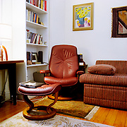 """A red """"Stressless"""" chair and footrest in the corner of a room, with a red fabric couch to its left, a pillow lying flat by the chair. There are small throw rugs on the wooden floor, a painting and a decorative rug on the wall, a bookcase next to the chair, and and a wooden table and lamp to the left."""