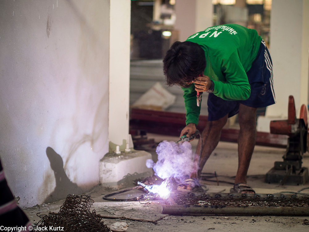 01 APRIL 2014 - BANGKOK, THAILAND:  A welder works in a nearly finished section of the Bangkok flower market. The Yodpiman Flower Market (also called Pak Khlong Talat) is being renovated and gentrified. The market opened in 1961 and has been a Bangkok landmark for more than 50 years, is being turned into a high end mall. Many of the flower and vegetable vendors in the market may be forced out.   PHOTO BY JACK KURTZ