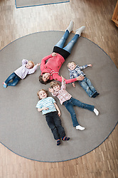 Female educator and four kids relaxing on ground in kindergarten, elevated view