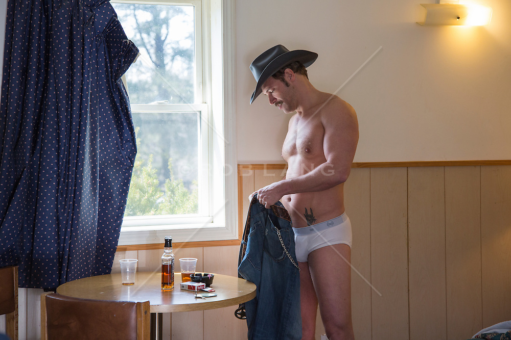 cowboy in his underwear taking money out of his wallet in a motel room