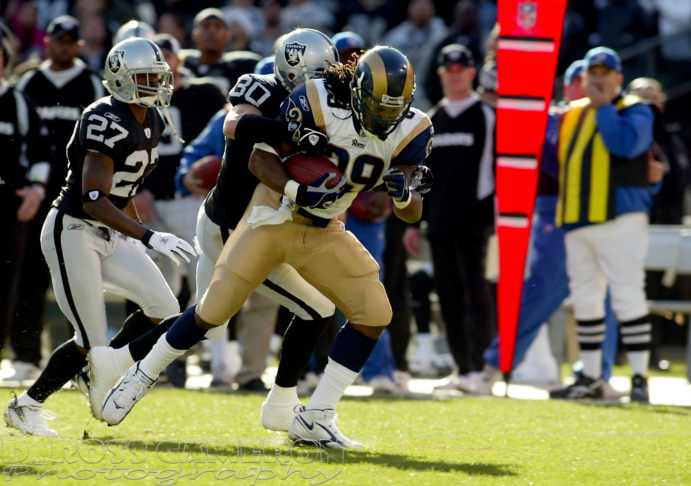 St. Louis Rams running back Steven Jackson (39) runs for a first down before being tackled by Oakland Raiders safety Stuart Schweigert (30) during the second quarter of an NFL football game, Sunday, Dec. 17, 2006 at McAfee Coliseum in Oakland, Calif. The Rams won, 20-0. (D. Ross Cameron/The Oakland Tribune)