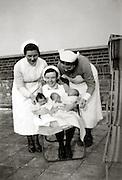 three nurses posing with newborn babies England 1930s