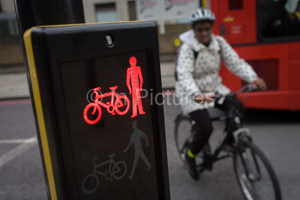 A cyclist braves London traffic by crossing the road on a red light. Rather than negotiate the road on a safe green light, the rider risks injury by fast-flowing traffic on the southern side of Westminster Bridge, on the Southwark side. Peddling over the highway, the young woman wears a helmet on her mountain bike. Cycling deaths in 2012 hit a five-year high, as 122 cyclists were killed on Britain's roads.