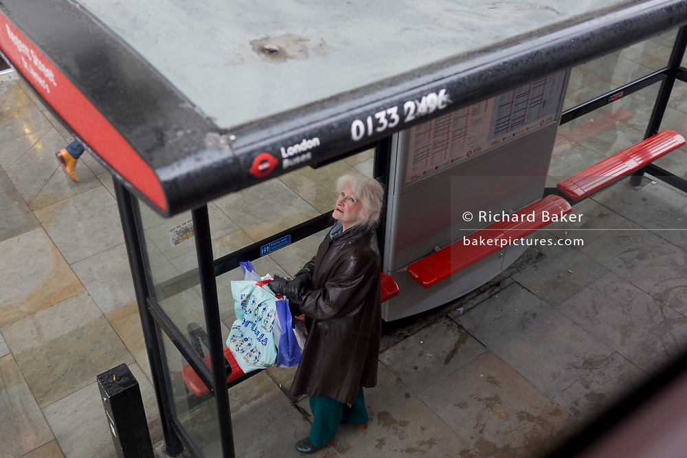 A lady looks up at due bus times, at a bus stop in central London, on 19th October 2017, in London, England.