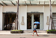 An office worker in fashionable apparel walks by the Chanel store in downtown Saigon on her way to work. Robert Dodge, a Washington DC photographer and writer, has been working on his Vietnam 40 Years Later project since 2005. The project has taken him throughout Vietnam, including Hanoi, Ho Chi Minh City (Saigon), Nha Trang, Mue Nie, Phan Thiet, the Mekong, Sapa, Ninh Binh and the Perfume Pagoda. His images capture scenes and people from women in conical hats planting rice along the Red River in the north to men and women working in the floating markets on the Mekong River and its tributaries. Robert's project also captures the traditions of ancient Asia in the rural markets, Buddhist Monasteries and the celebrations around Tet, the Lunar New Year. Also to be found are images of the emerging modern Vietnam, such as young people eating and drinking and embracing the fashions and music of the West. His book. Vietnam 40 Years Later, was published March 2014 by Damiani Editore of Italy.