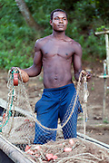 A portrait of a young fisherman mending his fishing nets at the end of the day. Praio Milao, Sao Tome. Sao Tome and Principe, are two islands of volcanic origin lying off the coast of Africa. Settled by Portuguese convicts in the late 1400s and later a centre for slaving, their independence movement culminated in a peaceful transition to self government from Portugal in 1975.