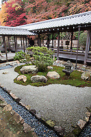 """Nanzenji is of the most powerful Zen monasteries in Japan, as it was counted among the Gozan, the five principal Zen establishments in Kyoto, and in 1381 was declared number one. Its main garden is a large rectangle of crushed rock, and can be viewed from verandas of Seiryoden Hall.  Along the eastern wall is a moss covered area containing large stones and shrubs, these elements arranged from north to south. Because Nanzenji is located just below the slope of Higashiyama, the view of the garden includes the borrowed scenery of the hillside. The shape of the boulders has led some to assume that they represent """"leaping tigers"""" following the Kano School paintings of tigers decorating the sliding doors of the Seiryoden Hall."""
