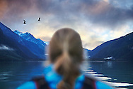 A view of the back of a woman's head as she gazes out across Chilkoot Lake at sunset.