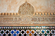 """Moorish arabesque ceramic tiles sculpted plasterwork of the Palacios Nazaries,  Alhambra. Granada, Andalusia, Spain. . The Alhambra is a palace and fortress complex located in Granada, Andalusia, Spain. It was originally constructed as a small fortress in 889 CE on the remains of ancient Roman fortifications. The Alhambra was renovated and rebuilt in the mid-13th century by the Arab Nasrid emir Mohammed ben Al-Ahmar of the Emirate of Granada, who built its current Alhambra palace and walls. The Alhambra was converted into a royal palace in 1333 by Yusuf I, Sultan of Granada. The decoration of The Alhambra consists for the upper part of the walls, as a rule, of Arabic inscriptions—mostly poems by Ibn Zamrak and others praising the palace—that are manipulated into geometrical patterns with vegetal background set onto an arabesque setting (""""Ataurique""""). Much of this ornament is carved stucco (plaster) rather than stone. Tile mosaics (""""alicatado"""") of The Alhambra, with complicated mathematical patterns (""""tracería"""", most precisely """"lacería""""), are largely used as panelling for the lower part. .<br /> <br /> Visit our SPAIN HISTORIC PLACXES PHOTO COLLECTIONS for more photos to download or buy as wall art prints https://funkystock.photoshelter.com/gallery-collection/Pictures-Images-of-Spain-Spanish-Historical-Archaeology-Sites-Museum-Antiquities/C0000EUVhLC3Nbgw <br /> .<br /> Visit our ISLAMIC HISTORICAL PLACES PHOTO COLLECTIONS for more photos to download or buy as wall art prints https://funkystock.photoshelter.com/gallery-collection/Islam-Islamic-Historic-Places-Architecture-Pictures-Images-of/C0000n7SGOHt9XWI"""