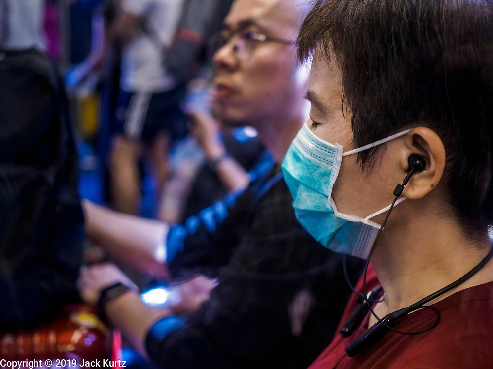"""14 JANUARY 2019 - BANGKOK, THAILAND:    A passenger wearing a dust filter on the skytrain in Bangkok. Bangkok has been blanketed by heavily polluted air for almost a week. Monday morning, the AQI (Air Quality Index) for Bangkok  was 182, higher than New Delhi, Jakarta, or Beijing. The Saphan Kwai neighborhood of Bangkok recorded an AQI of 370 and the Lat Yao neighborhood recorded an AQI of 403. An AQI above 50 is considered unsafe. Public health officials have warned people to avoid """"unnecessary"""" outdoor activities and wear breathing masks to filter out the dust.      PHOTO BY JACK KURTZ"""