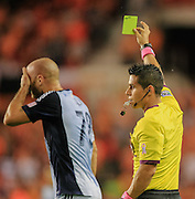 Oct 9, 2013; Houston, TX, USA; Referee Armando Villarreal issues a yellow card to Sporting KC defender Aurelien Collin (78) during the first half against the Houston Dynamo at BBVA Compass Stadium. Mandatory Credit: Thomas Campbell-USA TODAY Sports