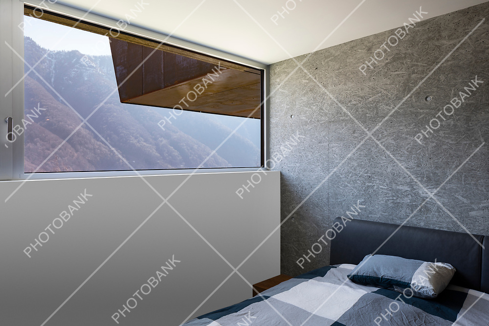 Bedroom detail with bed and pillow, large window overlooking the Swiss Alps. Nobody inside