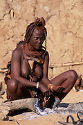 Himba woman & child beside trad- itional house. Kaokoland Namibia
