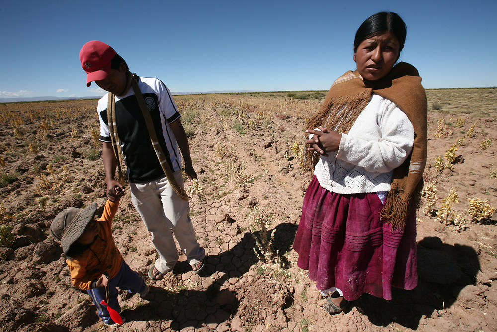 A Bolivian couple with their child on their field where their crop of quinoa failed this year because of frosts. Climate change is affecting the viability of farming in this area.