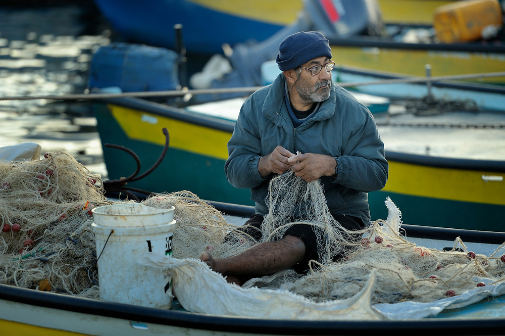 A fisher mends his nets after a night of fishing off Gaza's coast. Under the 1993 Oslo Peace Accords, the people of Gaza were allowed to fish out to 20 nautical miles from their coastline, yet since the Israeli military imposed a naval blockade in 2007 they have been limited to just three nautical miles. In practice, fishers who venture beyond two nautical miles are shot at by Israeli gunboats; several have been injured and some killed. Despite having 40 kilometers of coastline and a long tradition as fishers, many fishers are unemployed and the people of Gaza are forced to import fish from Israel. And what fishing they can do close to shore mostly involves the harvest of immature fish, which biologists warn has a negative impact on fish stocks in the region....