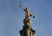 "The Lady of Justice statue atop The Central Criminal Court in England, commonly known as the Old Bailey from the street in which it stands, is a court building in central London, one of a number of buildings housing the Crown Court. The Crown Court sitting at the Central Criminal Court deals with major criminal cases from Greater London and, in exceptional cases, from other parts of England and Wales.<br /> <br /> On the dome above the court stands a bronze statue of Lady Justice, executed by British sculptor F. W. Pomeroy. She holds a sword in her right hand and the scales of justice in her left. The statue is popularly supposed to show blind Justice; however, the figure is not blindfolded: the courthouse brochures explain that this is because Lady Justice was originally not blindfolded, and because her ""maidenly form"" is supposed to guarantee her impartiality which renders the blindfold redundant."
