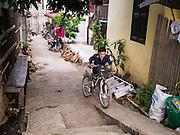 11 MARCH 2013 - LUANG PRABANG, LAOS:  A boy on his way to school pushes his bike up a narrow alley in Luang Prabang, Laos.   PHOTO BY JACK KURTZ