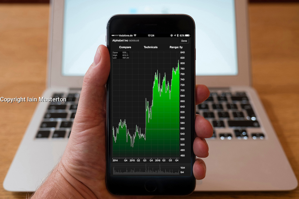 Using iPhone smartphone to display stock market performance chart for Google Alphabet company