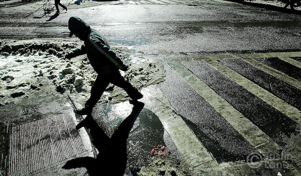 A pedestrian avoids a puddle on a street in New York, New York on Friday 16 February 2007. Two days after a winter storm covered New York with snow, temperatures remained low, but the sun turned much of the snow into slush and puddles.