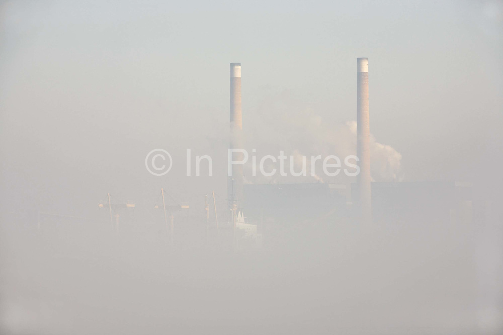 As winter fog lifts, the waters of the River Thames clear to reveal an eerie landscape of industrial river life and architecture at Gravesend, Kent England. It is late-morning and in the hazy distance on the northern river bank, steam clouds near the double twin chimneys of npower's 1400MW coal fired Tilbury power station (powering 1.4 million homes using 'biomass' fuels and low-sulphur coal) which rise above the passing ghostly bulk of a cargo freighter on its last miles of its voyage from open sea into the Thames Estuary and on to Tilbury Docks. Historically, the Thames has long been a route for shipping that kept the capital supplied and although the docks have seen huge decreases in traffic and volume since the second world war, Tilbury remains a busy hub for containerized vessels arrivng from all over the world.