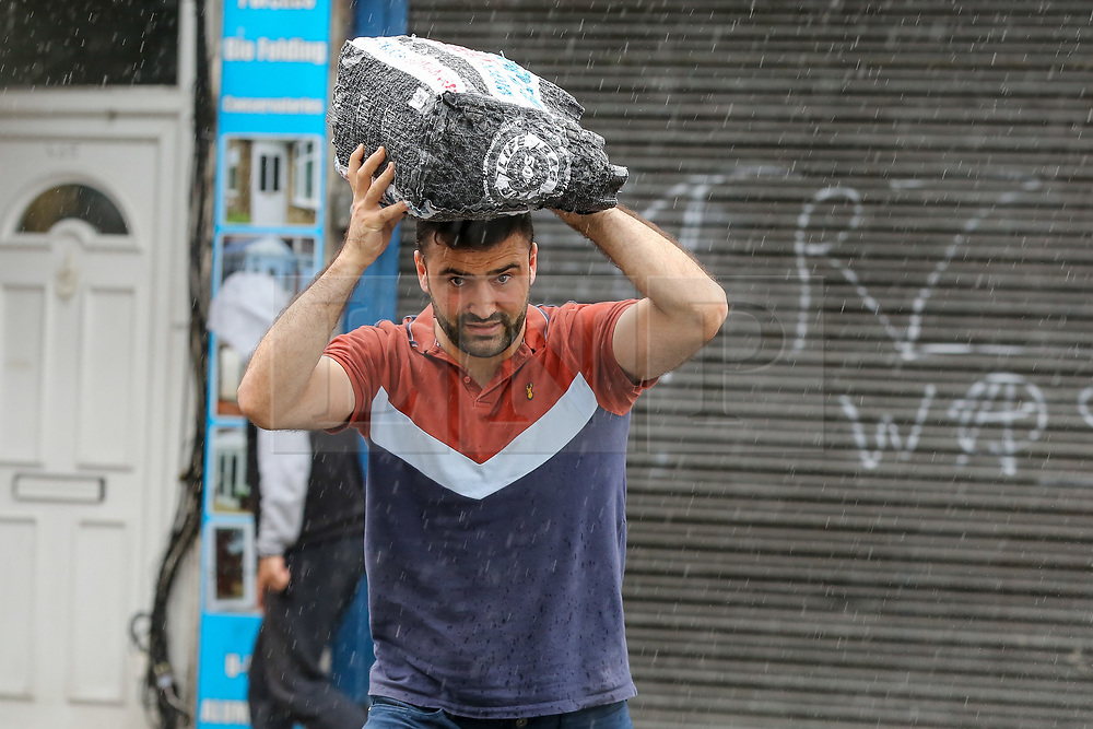 © Licensed to London News Pictures. 25/07/2021. London, UK. A man is caught out in a heavy downpour in north London., after the recent heatwave.  According to The Met Office, torrential thunderstorms are expected in the capital. Photo credit: Dinendra Haria/LNP