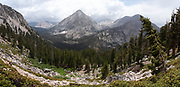 High angle view of a backpacker above Bubbs Creek and Vidette Meadow, with East Vidette Peak in the background; John Muir Trail/Pacific Crest Trail; Sequoia Kings Canyon Wilderness; Kings Canyon National Park; Sierra Nevada Mountains, California, USA.