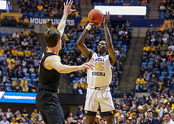 Jan 12, 2019; Morgantown, WV, USA; West Virginia Mountaineers forward Lamont West (15) shoots a three pointer during the second half against the Oklahoma State Cowboys at WVU Coliseum. Mandatory Credit: Ben Queen-USA TODAY Sports