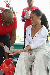 Rihanna takes part in a live HIV test, at the 'Man Aware' event held by the Barbados National HIV/AIDS Commission in Bridgetown, Barbados, during his tour of the Caribbean.