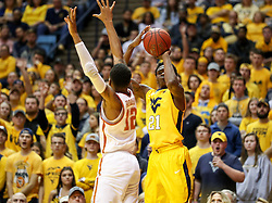 Jan 20, 2018; Morgantown, WV, USA; West Virginia Mountaineers forward Wesley Harris (21) shoots a three pointer over Texas Longhorns guard Kerwin Roach II (12) during the second half at WVU Coliseum. Mandatory Credit: Ben Queen-USA TODAY Sports