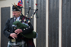 © under license to London News Pictures.  11/11/2010. A lone piper plays looking out over Plymouth. People around the UK have observed a two-minute silence to mark Armistice day. A lone bagpipe player at a war memorial in Plymouth.