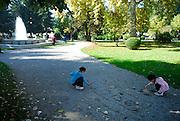 Children writing their names in gravel, Strossmayer Promenade (Strossmayerova setalista), town square park, with fountain in background. Petrinja, Croatia