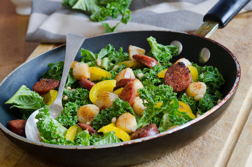 Spanish sausage, scallops, kale and yellow bell peppers in a pan
