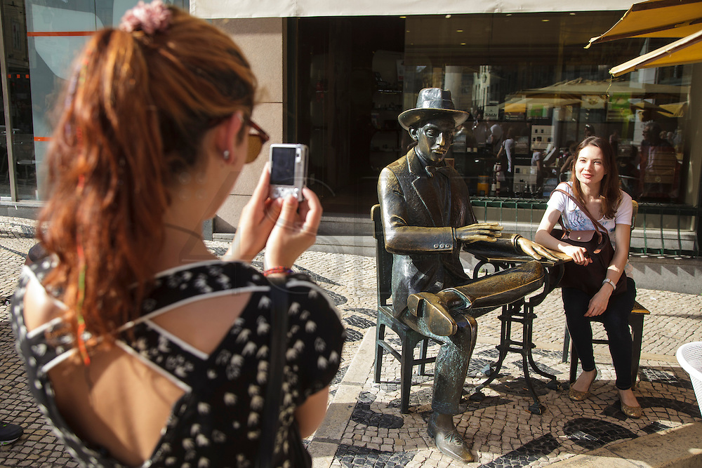 Tourists take pictures with Fernando Pessoa's statue in Chiado district. Fernando Pessoa is one of the two greatest poets in portuguese history, together with Luiz Vaz de Camões.