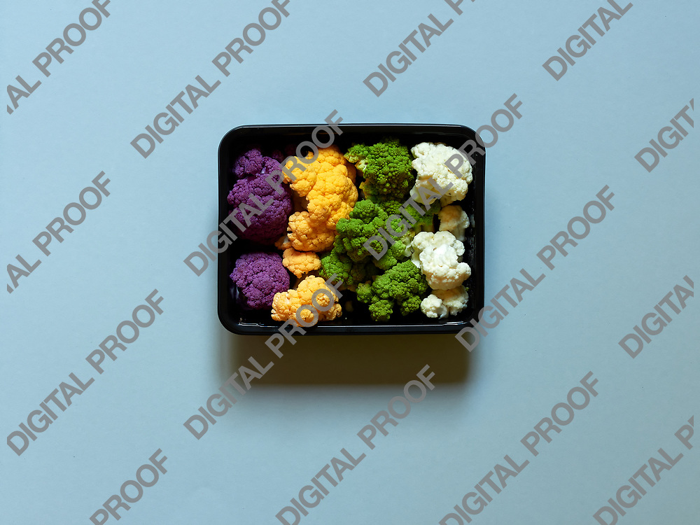 Set of seasonal and colorful cauliflower violet, yellow, green and white boxed in a plastic recipient over a pastel background