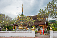 Young monks sweep at a temple in Luang Prabang.