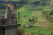 A griffin statue presides over the fortified walls of Orvieto, with the green countryside farms stretching out below. Orvieto, Umbria, Italy.