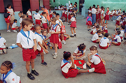 Primary school children eating packed lunches in playground during lunch break in Havana; Cuba,