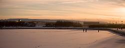 Family walking on ice in nice light of sunset - Fjölskylda á Reykjavíkurtjörn