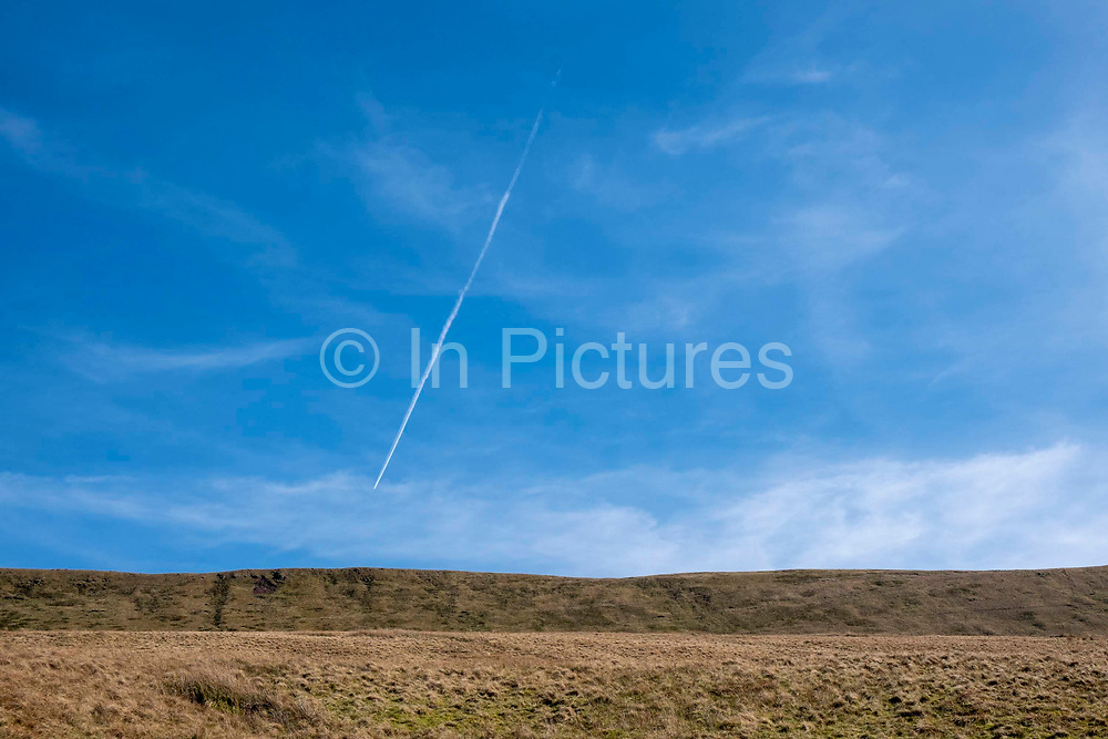 A condensation plane trail across a blue sky above the Pen Y Fan mountainside in Brecon Beacons National Park, Wales, Powys, United Kingdom.