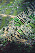 """From atop the peak of Huayna Picchu, see terraces of the Machu Picchu archeological site in the Cordillera Vilcabamba, Andes mountains, Peru, South America. The Incas built temples, terraces, and a trail up the peak of Huayna Picchu (""""Young Peak"""" in Quechua, 2720 meters or 8920 feet above sea level). Machu Picchu was built around 1450 AD as an estate for the Inca emperor Pachacuti (14381472). Spaniards passed in the river valley below but never discovered Machu Picchu during their conquest of the Incas 1532-1572. The outside world was unaware of the """"Lost City of the Incas"""" until revealed by American historian Hiram Bingham in 1911. Machu Picchu perches at 2430 meters elevation (7970 feet) on a well defended ridge 450 meters (1480 ft) above a loop of the Urubamba/Vilcanota River ( Sacred Valley of the Incas). UNESCO honored the Historic Sanctuary of Machu Picchu on the World Heritage List in 1983."""