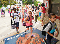 A combination of excitement and jitters as 1st and 2nd graders head into Elm Street School on their first day Tuesday morning.  (Karen Bobotas/for the Laconia Daily Sun)