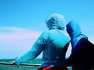 Friends wearing blue windbreakers look over the side of a boat sailing between Koh Phi Phi and Phuket, Thailand, Southeast Asia