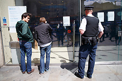 © licensed to London News Pictures. London, UK 12/05/2014. Police officers investigating a Barclays Bank branch in Piccadilly Circus in central London after a robbery has taken place at the bank on Monday, 12 May 2014. Photo credit: Tolga Akmen/LNP