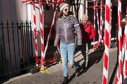 Passers by wearing stripes pass red and white striped warning tapeon scaffolding in London, UK.