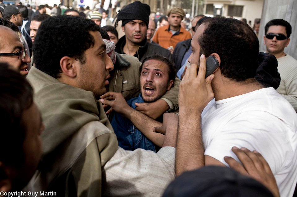 A Mobarack supporter and alleged secret policeman is surrounded, violently beaten and dragged towards the makeshift interogation rooms in Tahrir square where government supporters are held.