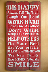 Collection of unusual inspirational and motivational quotes on a wooden board mounted on wall, South Africa