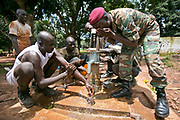 Soldiers from former Seleka rebels, who took over the former presidential guard's training camp in Bossembele, help the ICDI mechanical team repair the broken water pump. After the ICDI mechanical team had fixed the broken water pump, the soldiers, both in and without uniforms, feel for the water for the first time since March, 2013.