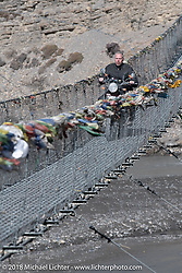 Denver Joe Hicks riding across a narrow suspension bridge over the Kali Gandaki River on day-6 of our Himalayan Heroes adventure riding from Muktinath to Tatopani, Nepal. Sunday, November 11, 2018. Photography ©2018 Michael Lichter.